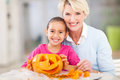 Girl grandmother halloween beautiful little and making pumpkin together Stock Photos