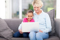 Girl grandmother laptop cheerful little and her using a at home Royalty Free Stock Photography