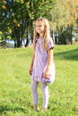 Girl on grass barefoot smiling kid in lila dress standing Stock Photography
