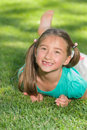 Girl on grass a with long brown hair in pigtails and brown eyes who just lost her two front teeth smiles as she lays the in her Stock Image