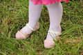 Girl on grass in pink shoes Stock Photos