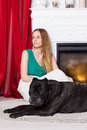 Girl in green dress sitting by the fireplace with dog Cane Corso Royalty Free Stock Photo