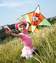 Girl in green grass fly kite. Royalty Free Stock Images
