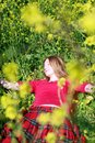 Girl in green grass and yellow flowers Royalty Free Stock Image