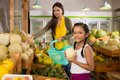 Girl at grocery store smiling indian with a fresh melon standing the Royalty Free Stock Images