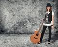Girl with the guitar gray concrete wall Royalty Free Stock Photography