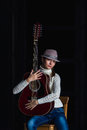 Girl with guitar in a hat a sitting on a bar stool Stock Image