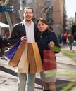Girl and guy with purchases in black jackets at street Stock Photo