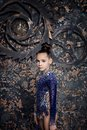 Girl gymnast in a blue suit with sparkles