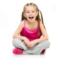 Girl gymnast smiling little in studio on a white background Stock Image