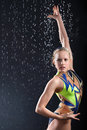 Girl gymnast takes graceful pose in rain Royalty Free Stock Photo