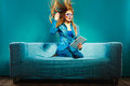 Girl hair blowing with tablet on couch Royalty Free Stock Photo