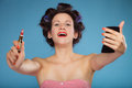 Girl in hair curlers applying red lipstick Royalty Free Stock Photo