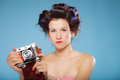 Girl in hair curlers taking picture with old camera pretty using vintage blue background Royalty Free Stock Photography