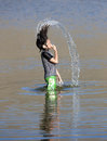 Girl hair flips with water a dunks her head in then whips it out making a stream of Royalty Free Stock Photo