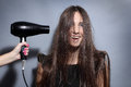 Girl with hairdryer dries long hair Royalty Free Stock Photography