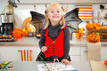 Girl in halloween bat costume drawing Jack-O-Lantern on paper Royalty Free Stock Photo