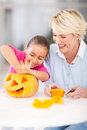 Girl halloween pumpkin granny excited little cleaning her with at home Stock Photography