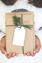 Girl hand holding craft and handmade christmas present gift boxes with tag. Royalty Free Stock Photo