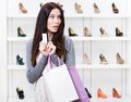 Girl hands credit card in footwear shop holds with great variety of stylish shoes Stock Photo