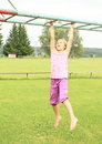 Girl hanging on obstacle course barefoot strong kid with opened mouth and tongue out Stock Photography