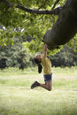 Girl Hanging From Tree Branch Royalty Free Stock Photo