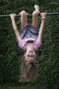 Child hanging upside down on climbing frame Royalty Free Stock Photo