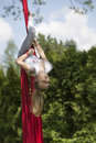 Girl hanging upside down from fabric red outdoors Royalty Free Stock Photos