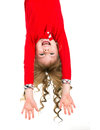 Girl hanging upside down little beautiful in red clothes with long blond curls isolated on white Royalty Free Stock Image