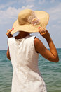 Girl in a hat on the beach photo shows beautiful she is wearing white dress and Royalty Free Stock Image