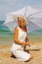 Girl in a hat on the beach photo shows beautiful she is wearing white dress and white white umbrella hand Stock Images