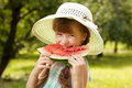 Girl in the hat and dress eating a watermelon Stock Photo