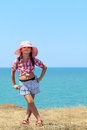 Girl in a hat full length stands with his legs crossed on background of the sea Royalty Free Stock Images
