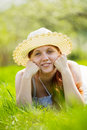 Girl in hat lying at meadow Stock Images