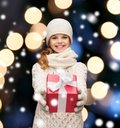 Girl in hat muffler and gloves with gift box christmas x mas winter happiness concept smiling Royalty Free Stock Photography
