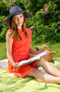 Girl in a hat reading a magazine on the nature Royalty Free Stock Photography