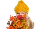 Girl in hat and scarf hiding behind autumn bouquet isolated on white Royalty Free Stock Photography