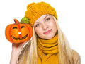 Girl in hat and scarf showing jack o lantern isolated on white Royalty Free Stock Image