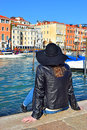 Girl in hat sits on the embankment of Grand Canal in Venice Royalty Free Stock Photo