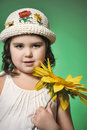 Girl in a hat in the studio on a green background with sunflower Royalty Free Stock Photo