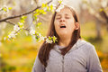 Girl holds a dandelion and sneezes.
