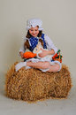 Girl in the hay feeding the easter bunny carrots Stock Photos