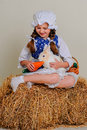 Girl in the hay feeding the easter bunny carrots Royalty Free Stock Images
