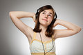 Girl with headphones on gray background Stock Image