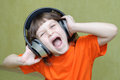 Girl with headphones on head singing loudly beautiful her and an orange shirt shouts Royalty Free Stock Images