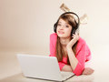 Girl with headphones and laptop listening to music Royalty Free Stock Photo