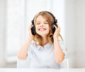 Girl with headphones listening to music home technology and concept little and singing Royalty Free Stock Images