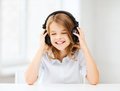 Girl with headphones listening to music home technology and concept little and singing Royalty Free Stock Photography