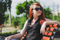 Girl with headphones red haired in on the bench Royalty Free Stock Photos