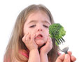 Girl and healthy broccoli diet on white a young is making a funny disgusting face at a fork with a piece of a background Stock Photo